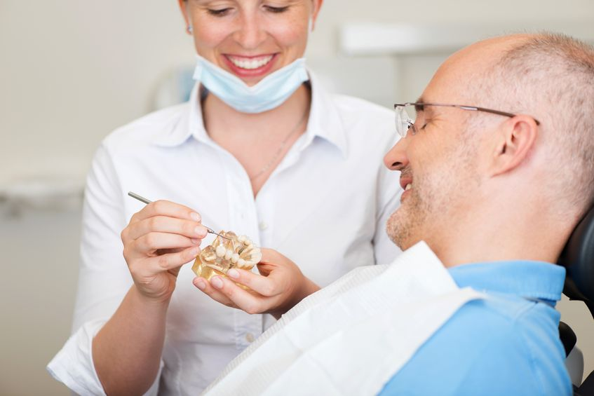 21246833 - smiling female dentist explaining artificial teeth to patient in clinic