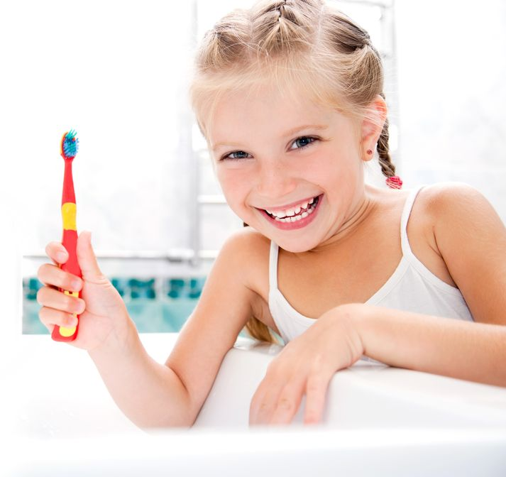14767428 - little girl brushing teeth in bath