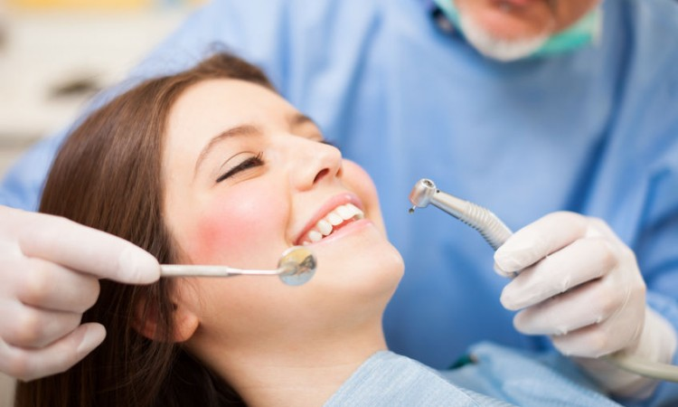 22208793 - dentist doing a dental treatment on a female patient