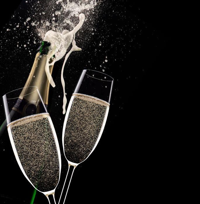 33557889 - champagne flutes on black background, celebration theme.