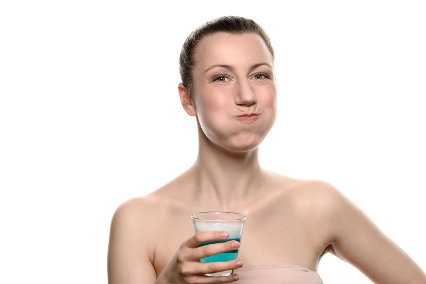 39843081 - healthy happy woman rinsing and gargling while using mouthwash from a glass, during daily oral hygiene routine, portrait with bare shoulders, with copy space, isolated on white