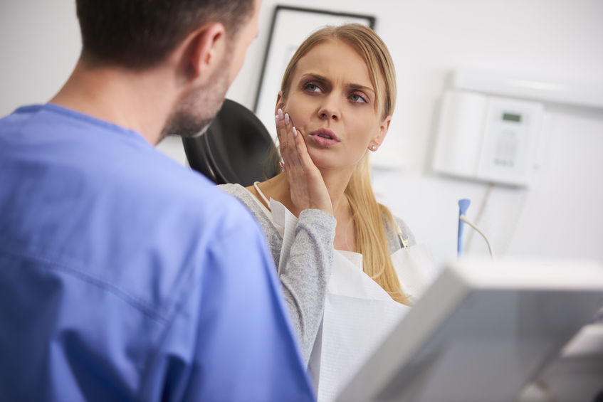 Woman with toothache talking to dentist