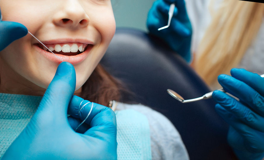 Cut view hands in latex gloves to floss child front teeth. Woman hold dental tools beside