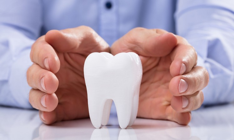 Man's Hand Protecting Healthy Hygienic White Tooth On Reflective Table