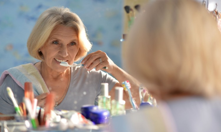Portrait of happy senior woman brushing her teeth