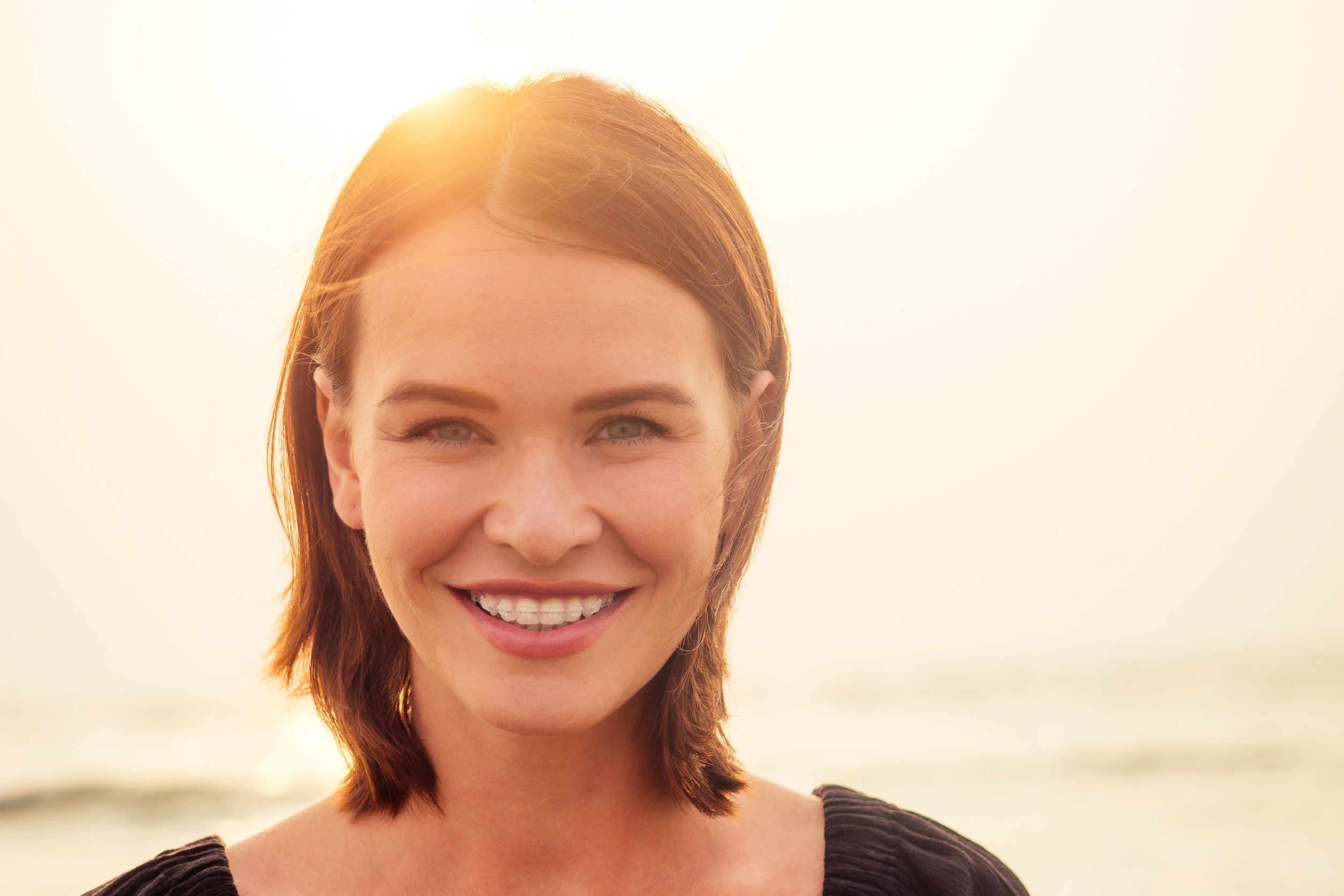 woman, 30-35 years old smiling toothy smile with braces on sea ocean beach background.spf and sunscreen.
