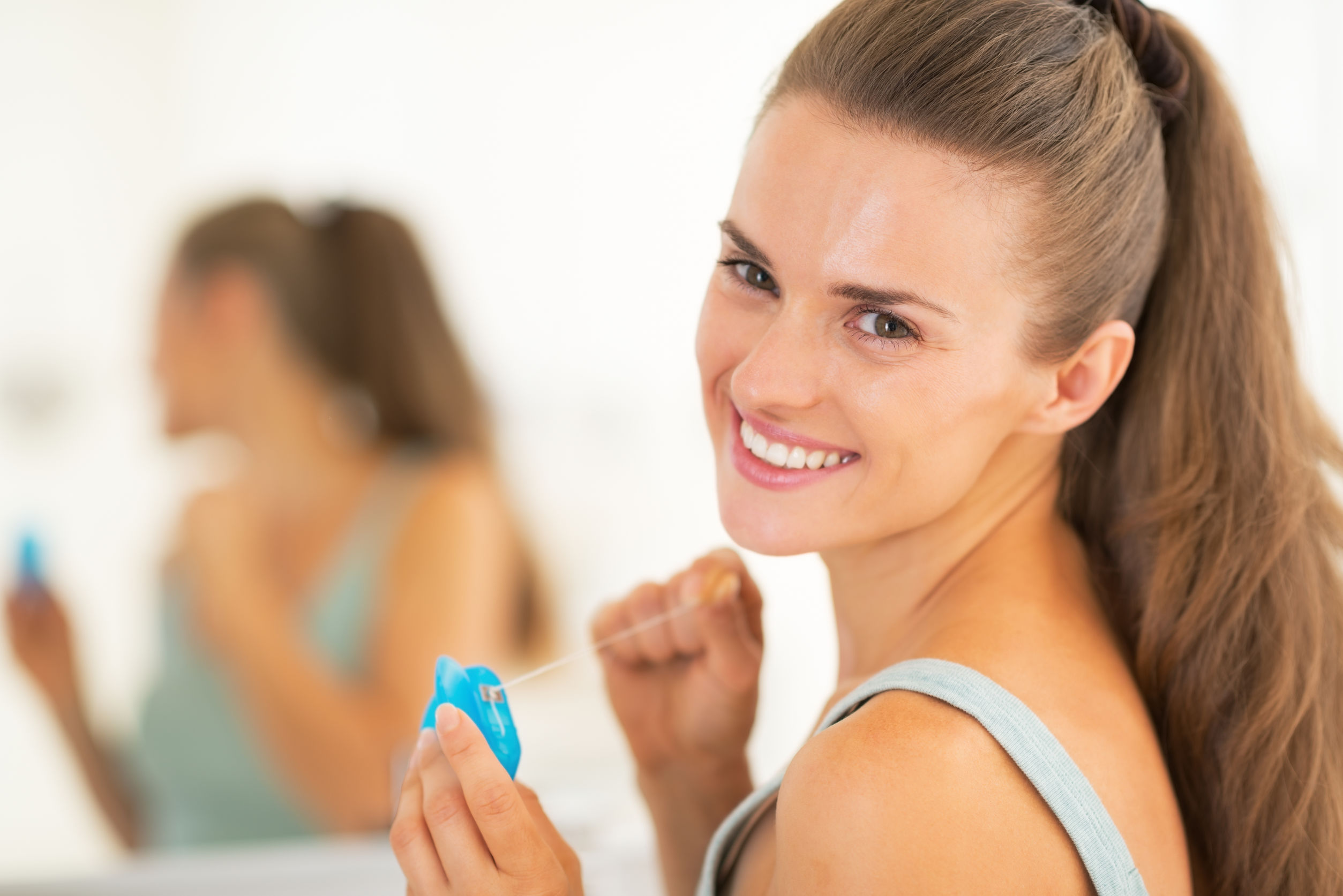 Portrait of happy young woman with dental floss