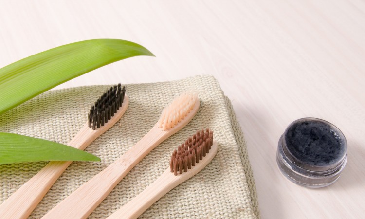bamboo toothbrushes on natural coarse cloth on a wooden table, homemade charcoal toothpaste in a small glass jar, leaves long plants, eco friendly life style concept