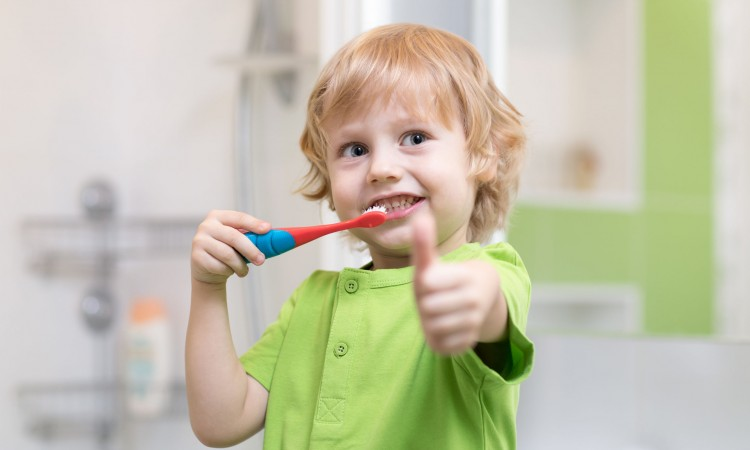 Little kid boy brushing his teeth in the bathroom. Smiling child holding toothbrush and showing thumbs up.
