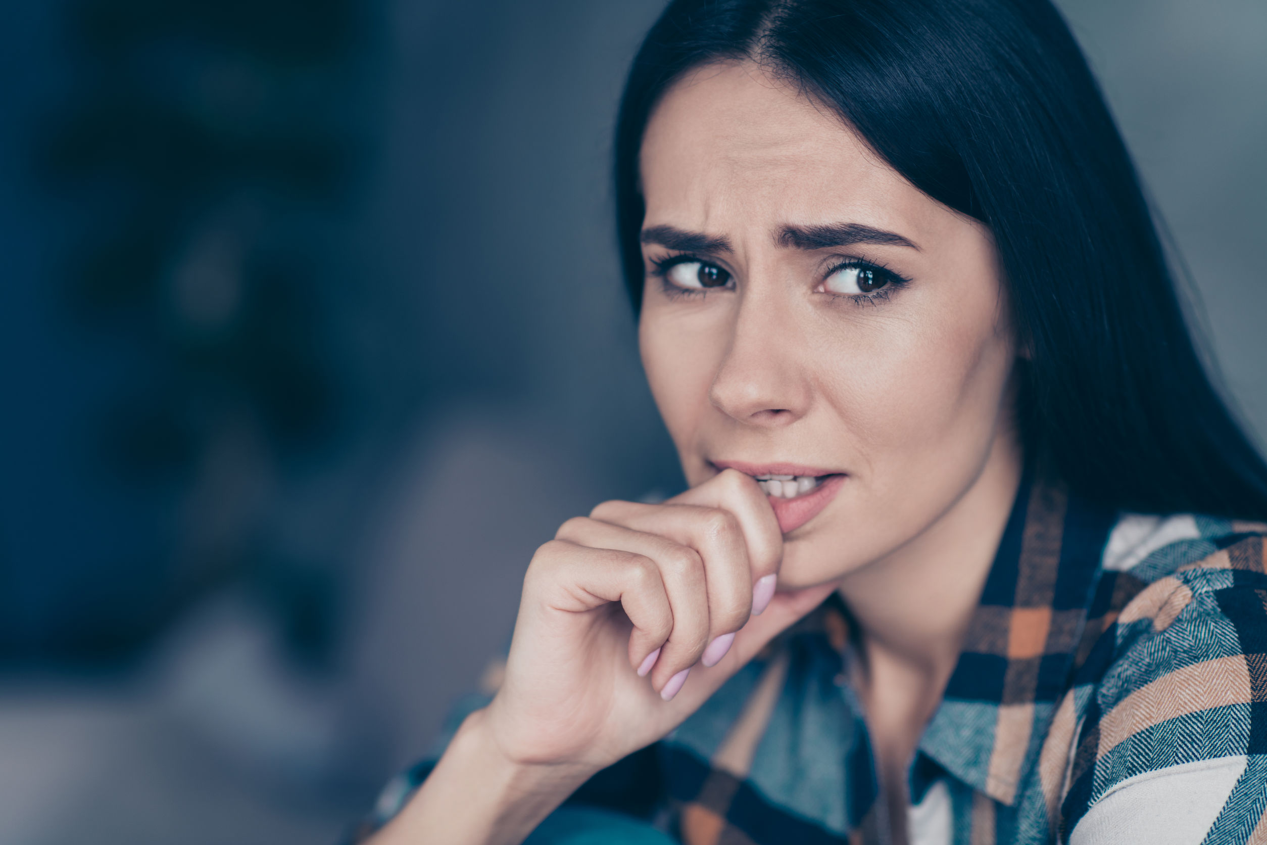 Close up side profile photo she her lady displeased hopeless arm hand bite, fingers nerves made mistake have doubts tell or no wear checkered plaid shirt sit lean divan flat house living room indoors