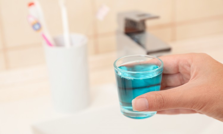Woman holding glass with mouthwash for teeth and oral care in bathroom