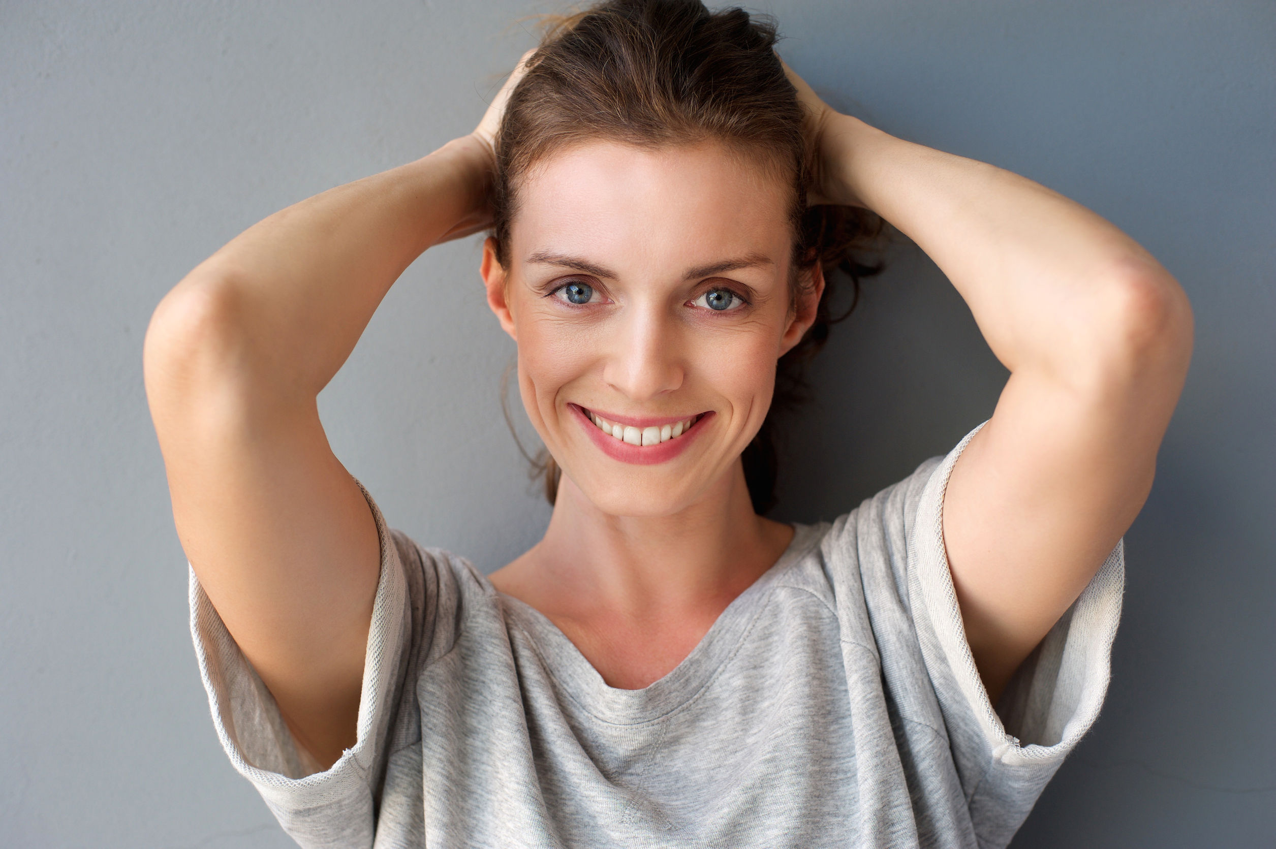 37864615 - close up portrait of a happy mid adult woman smiling with hands in hair against gray background