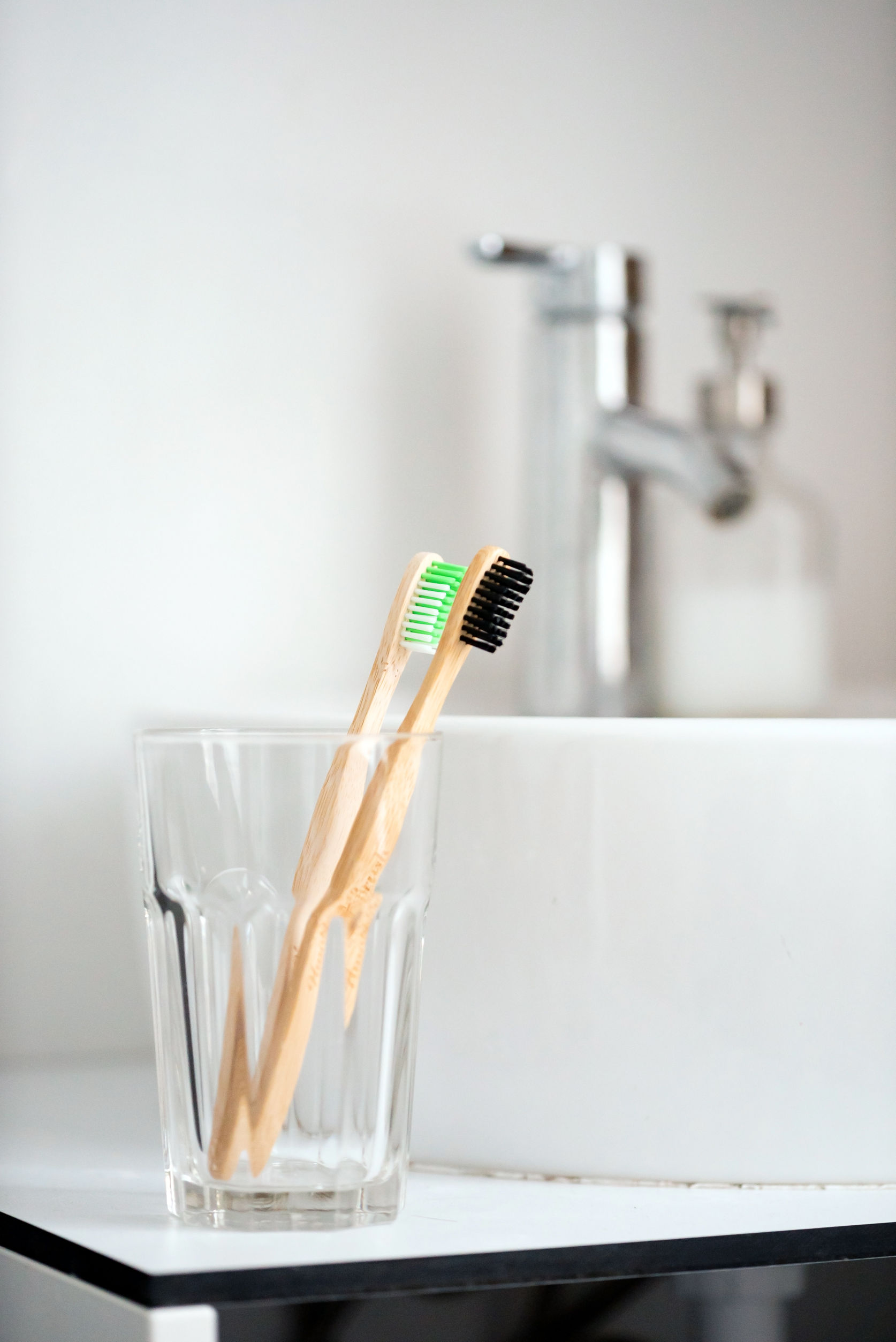 eco natural bamboo toothbrushes in glass. sustainable lifestyle concept. zero waste home. bathroom essentials, plastic free items