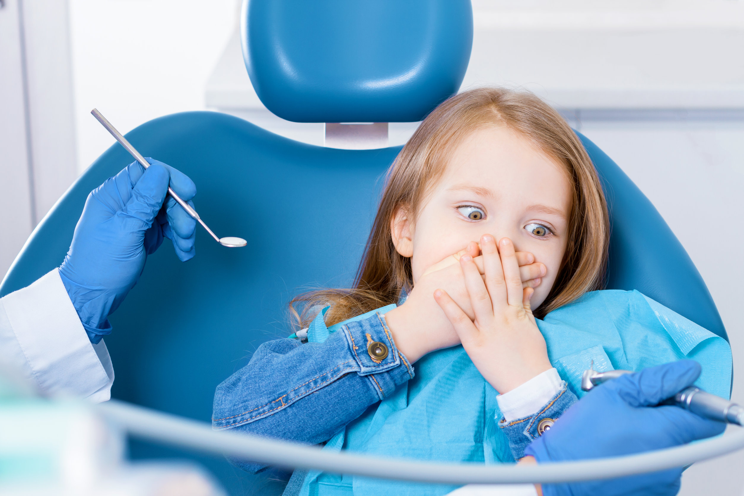 Little cute girl is closing her mouth with hands, preventing examination of teeth, because of fear of doctor. Child is sitting in chair in dental clinic, office. Visiting dentist with children.